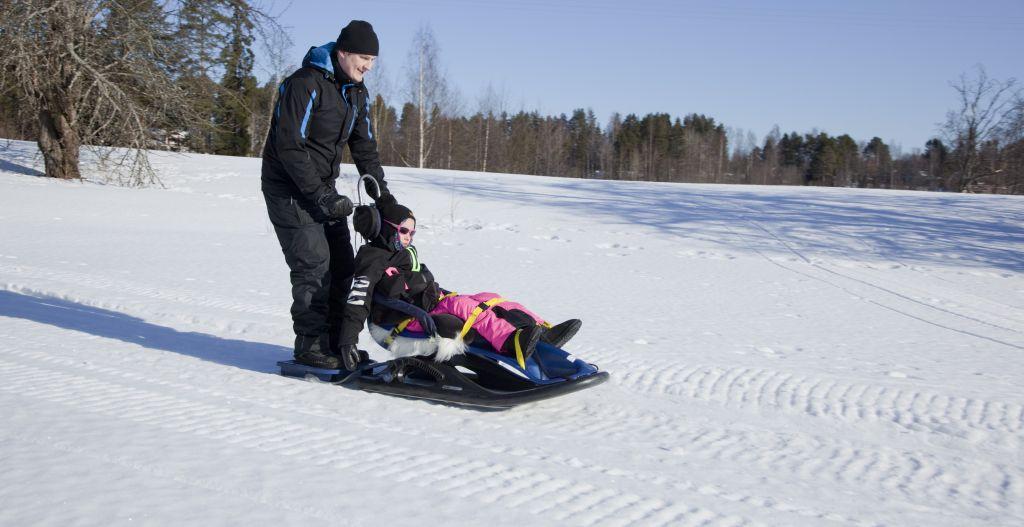 On aurinkoinen talvipäivä ja vaikesti vammainen tyttö laskee isänsä kanssa mäkeä Snow Comfort -kelkalla. Tytölle on kelkassa pään- ja vartalontuki. Isä seisoo kelkan takana olevalla jalustimella. Maisema on avara, luminen ja loiva mäki. Taustalla näkyy puita.