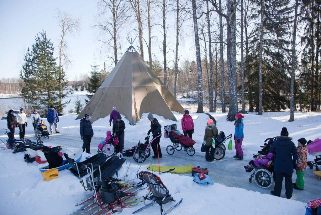 On talvi, taustalla näkyy kotateltta ja joki. Kodan edessä seisoo aikuisia ihmisiä ja muutama lapsi istuu rattaissa tai maastopyörätuolissa. Etualalla hiihtokelkkoja, pulkkia ym. toimintavälineitä hangella.