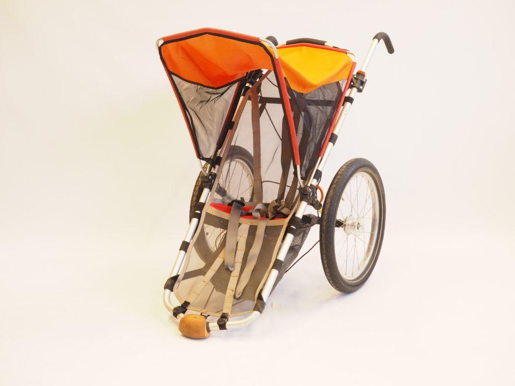 Kevytrakenteiset maastorattaat. Rattaissa on kaksi isoa rengasta ja työntökahvat. Oranssi aurinkosuoja sekä kankainen istuinosa.