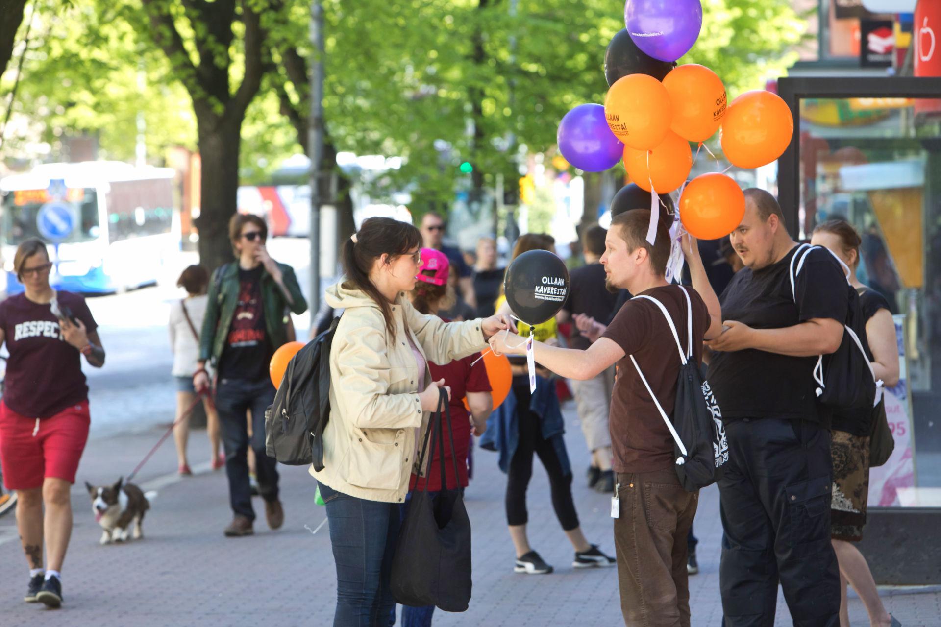Vapaaehtoiset jakavat ilmapalloja Tampereen Hämeenkadulla