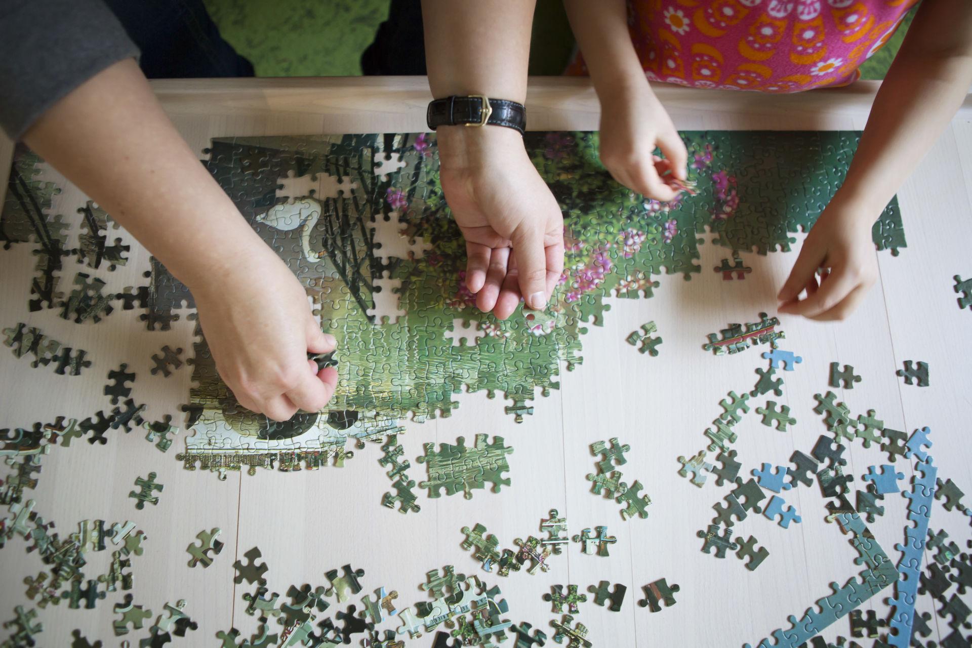 Aikuisen ja lapsen kädet tekemässä palapelia.