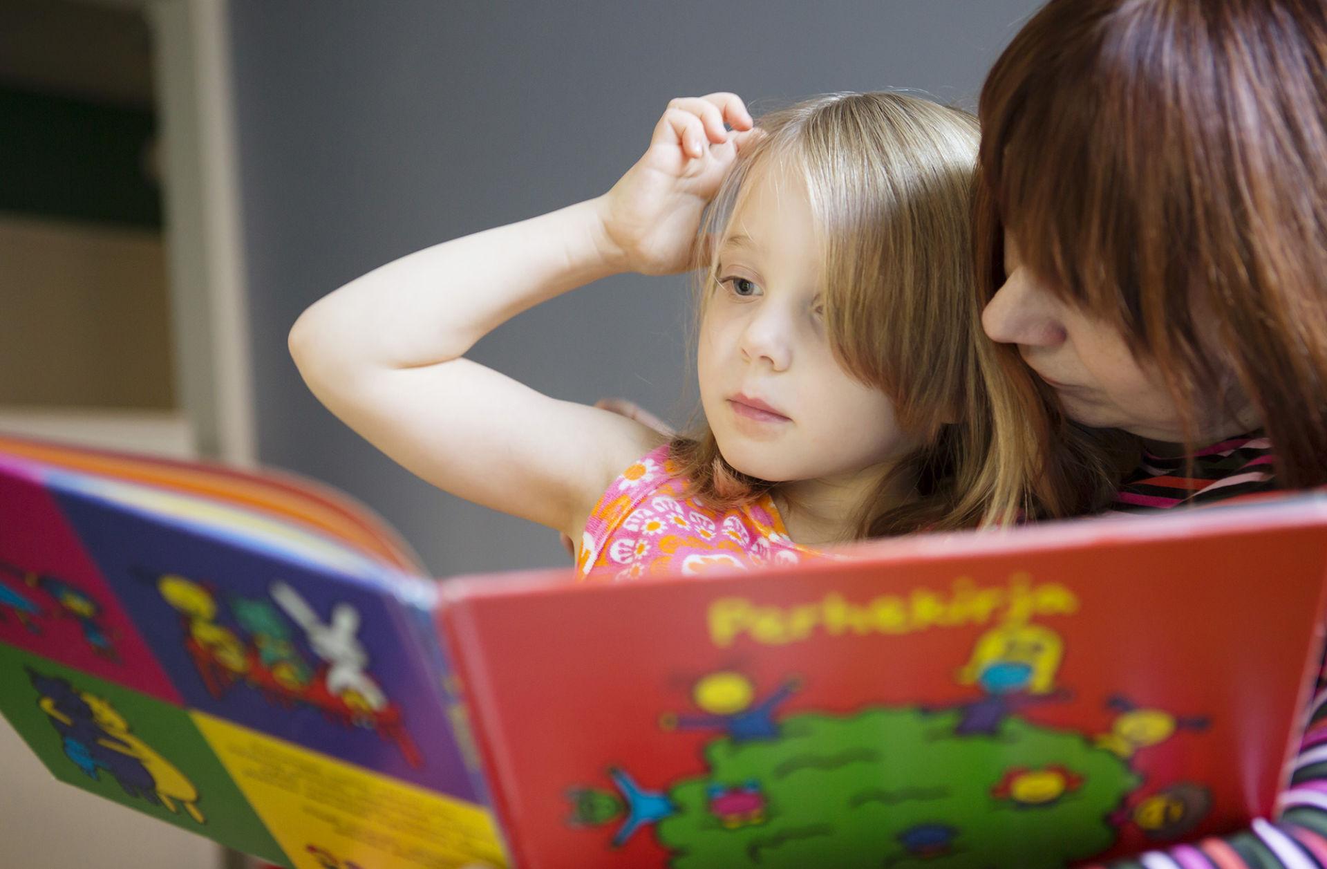Tyttö ja täti lukevat yhdessä kirjaa.
