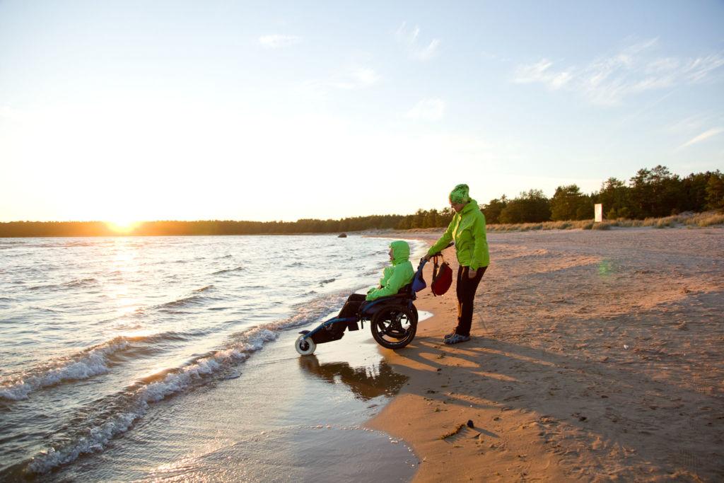 Kaksi henkilöä katselee auringon laskua hiekkarannalla. Toinen heistä istuu Hippocampe-maastopyörätuolissa ja toinen työntää maastopyörätuolia. Kuva: Janne Ruotsalainen