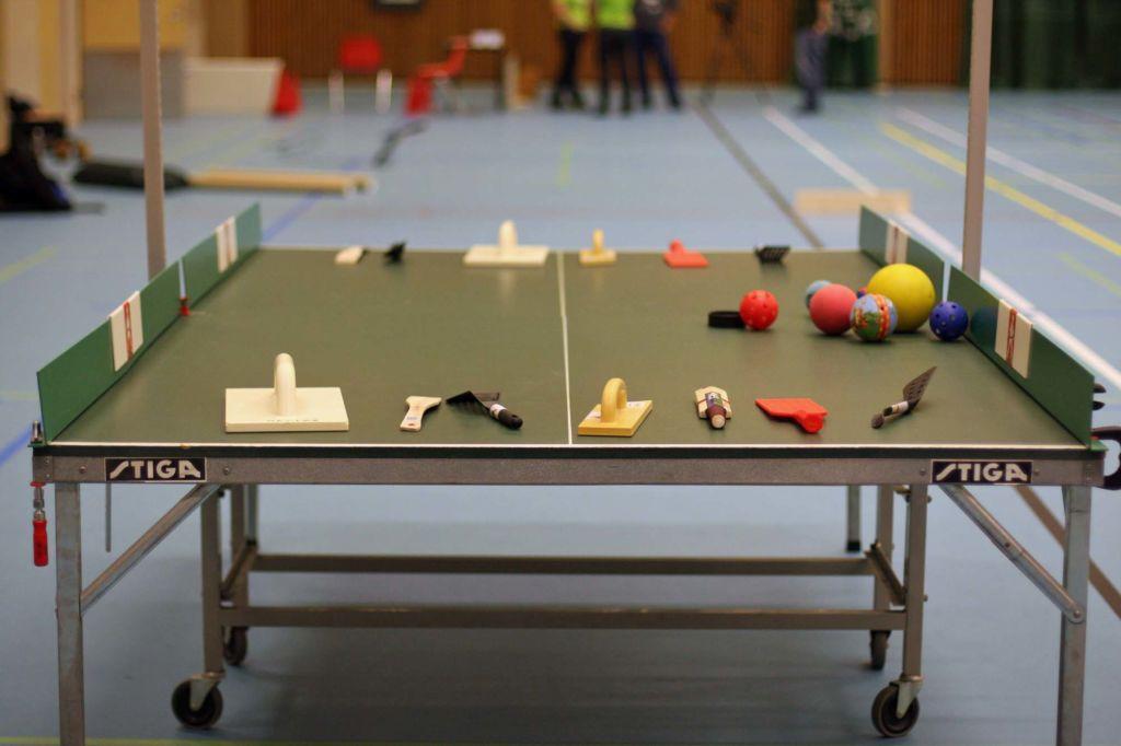 Liikuntasalissa olevan pingispöydän päälle on aseteltu erilaisia mailavaihtoehtoja pöytäpeliin. Pöydällä on muun muassa puinen ja muovinen maila, seinätasoitin ja paistinlasta, joilla voi pelata pöytäpeliä.