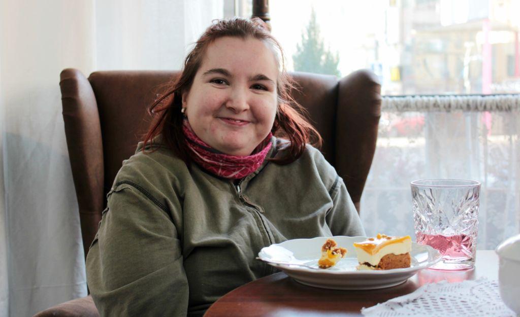Kuvassa Niina Jäntti istuu hymyillen kahvilassa