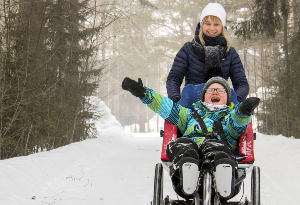 On talvi ja hieman sumuinen ilma. Kuvan oikeassa reunassa näkyy poika, joka istuu Kangoo Monitoimirattaissa kädet ylös kohotettuina ja nauravana. Nainen työntää rattaita. Kuvan vasemmassa reunassa näkyy lunta ja puita sumuharson takana.