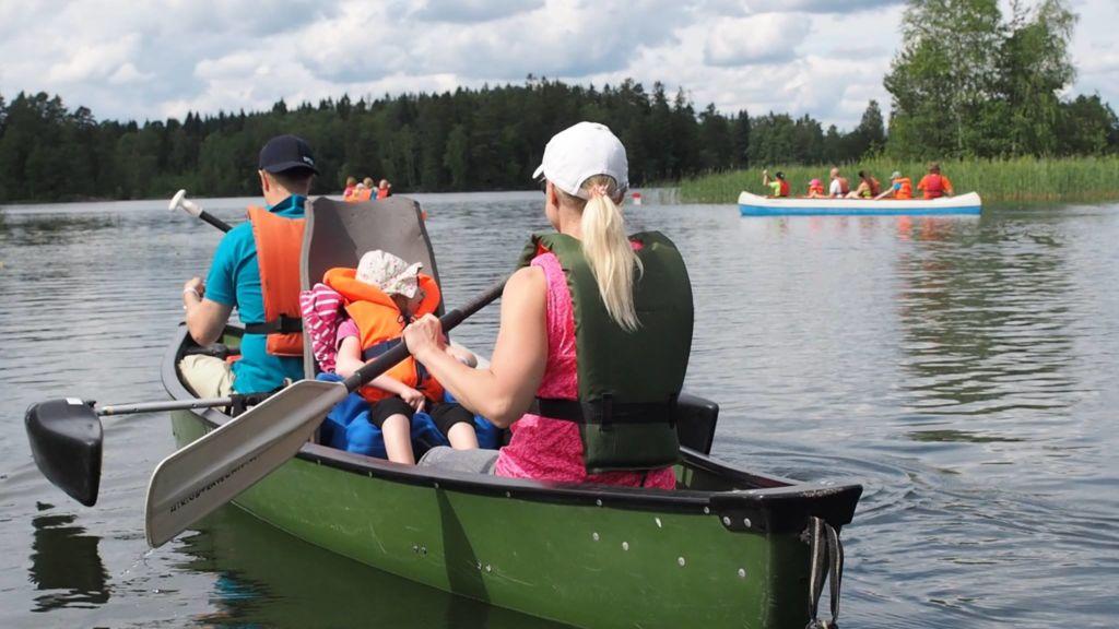 Kanootissa istuu nainen, lapsi ja mies. Lapsi istuu korkeaselkänojaisessa kanoottituolissa. Nainen ja mies melovat. Taustalla näkyy kaksi muuta kanoottia, joissa ihmisiä melomassa järvellä..
