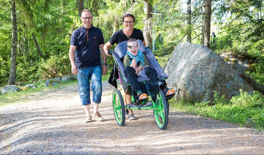 Vaikeasti vammainen poika retkerilemässä toimintavälineen ja vanhempiensa avustamana.
