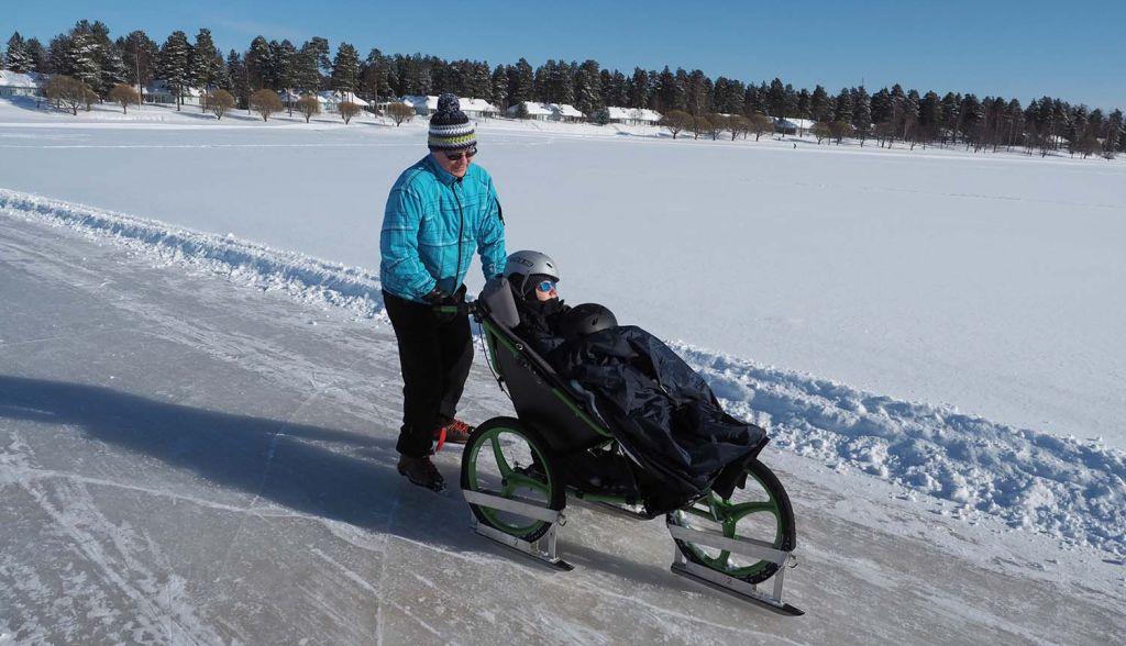 On aurinkoinen talvipäivä, kaksi miestä on luistelemassa järven jäällä olevalla luistelureitillä. Toinen miehistä istuu Largo-rattaissa, joiden renkaisiin on kiinnitetty luistimet ja toinen miehistä työntää rattaita.