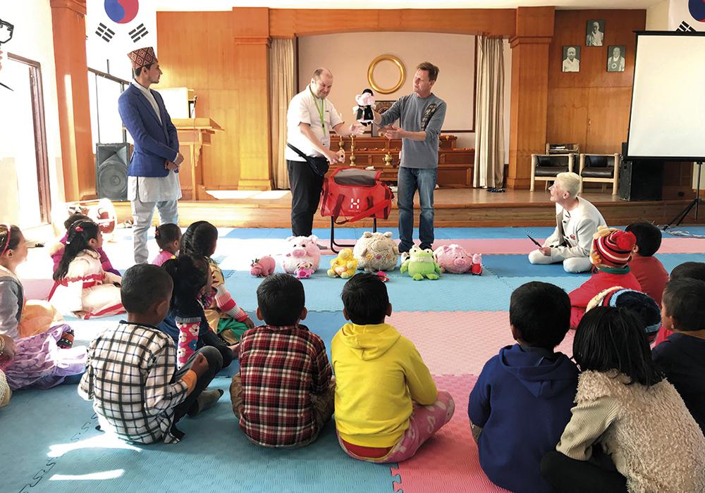 Mies puhuu lapsille. Lapset istuvat lattialla.