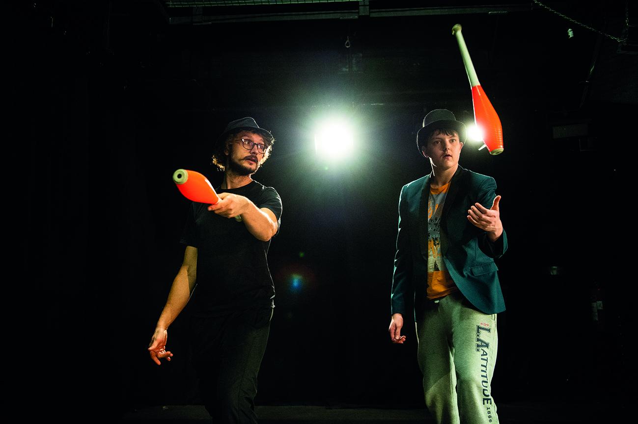 Kaksi miestä harjoittelee sirkustemppuja.