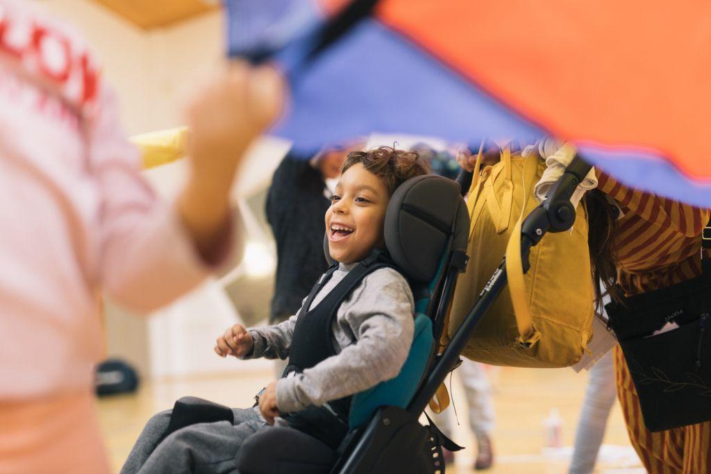 Jacob Anttilaa naurattaa leikkivarjon alla perheiden MAHTI-kurssilla Turussa. Kuva: Johannes Romppanen