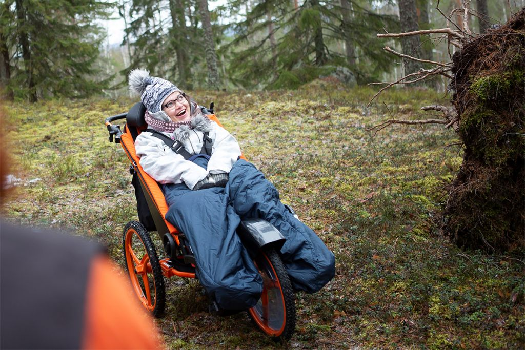 Nainen metsäretkellä. Hänellä on käytössään Largoo-maastorattaat ja hän katsoo nauraen ylöspäin.
