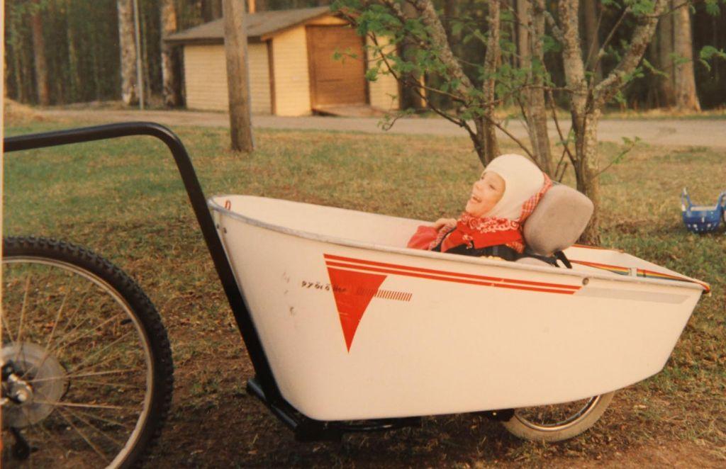 Vanha valkoinen polkupyörän peräkärry Malikkeen alkuajoilta. Peräkärryssä istuu nauravainen tyttö, taustalla nurmikenttää ja lautarakenteinen beige autotalli.