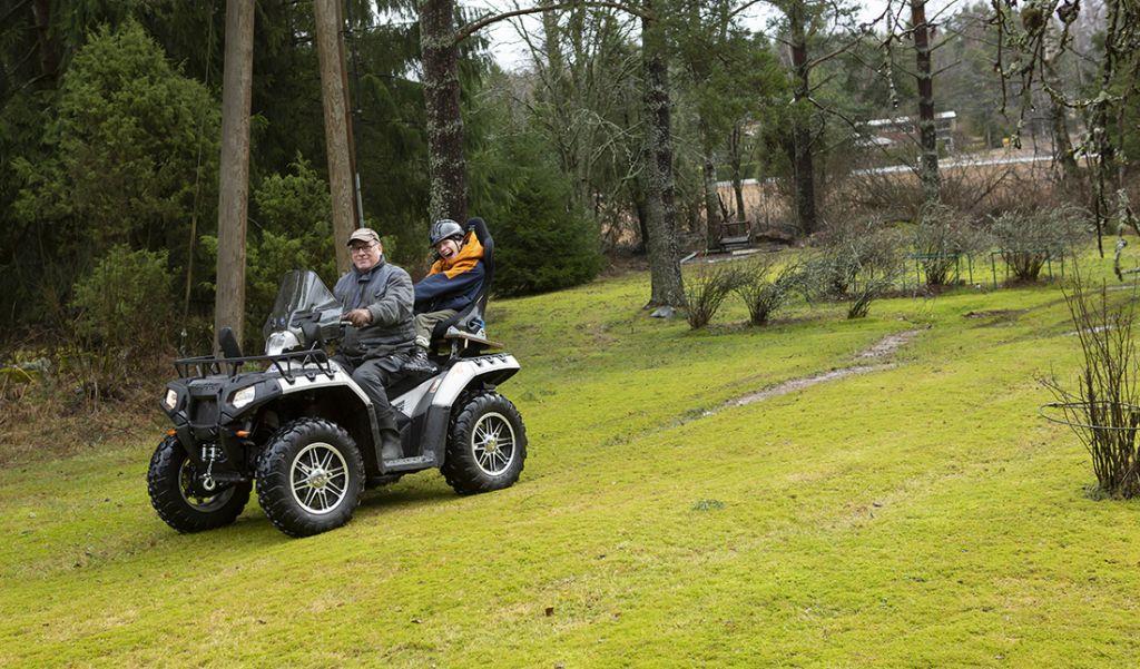 Lauri ja isä Teemu ajavat mönkijällä pihamaalla.