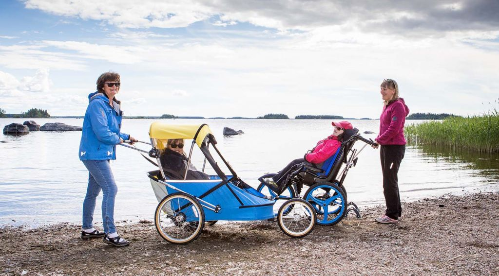 On syksy, kaksi nuorta naista istuu maastokärryissä hiekkarannalla, meri on tyyni. Molempien maastokärryjen takana seisoo nainen pidellen kiinni työntöaisasta.Kuva: Ann-Britt Bada