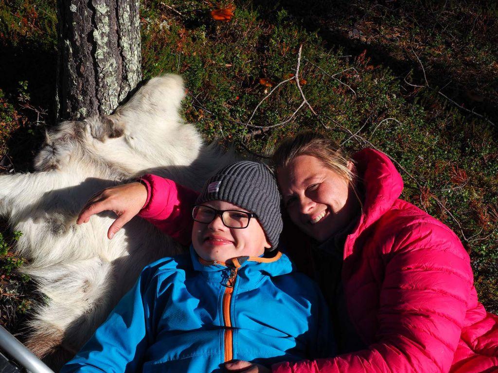 Poika ja nainen makoilevat porontaljalla syksyisessä metsässä. Molemmat hymyilevät.