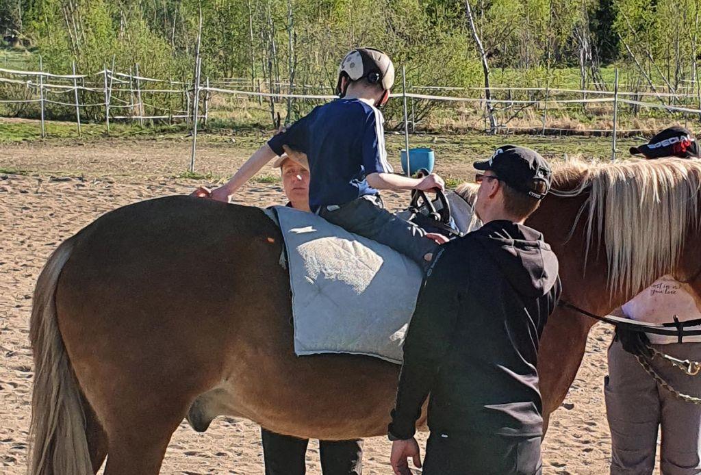 Terapiavyön avulla ratsastaessaan 10-vuotias Olli Juntunen saa kokea ohjaavansa hevosta itse. Kuva: Juntusen perhealbumi