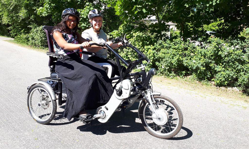 Kaksi naista pyöräilee rinnakkain poljettavalla tandempyörällä. On kesä ja aurinko paistaa. Taustalla näkyy pensaita ja puita.