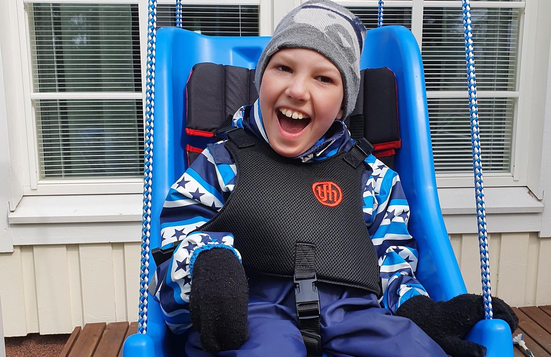 Vaikeasti vammaInen Olli Juntunen viihtyy aurinkokeinussa, joka tukee hänen asentoaan. Kuva: Juntusten perhealbumi.