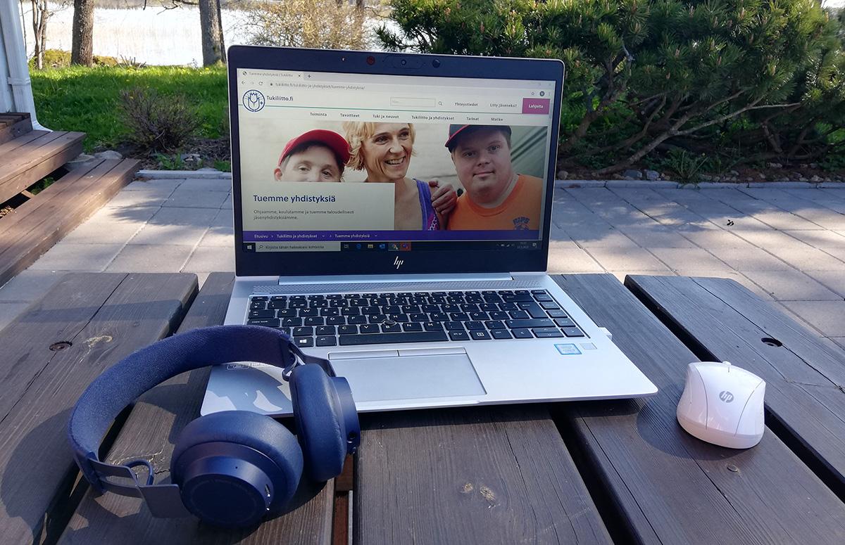 tietokone ja kuulokkeet pihapöydällä