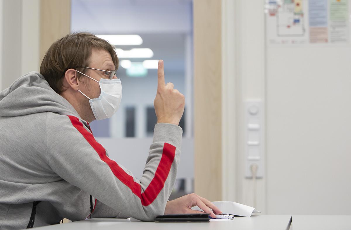 Sami Korhonen pitää koronaviruksen takia suojamaskia kokouksessa.
