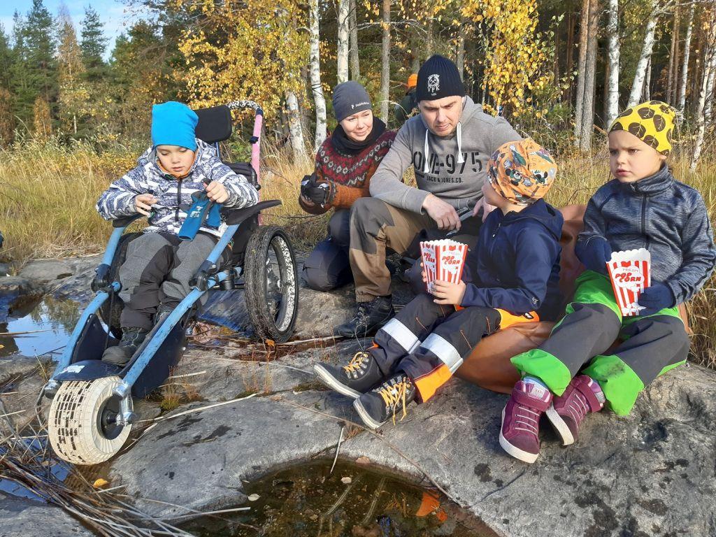 Perhe ulkoilee syksyisessä luonnossa Nurmeksessa. Vaikeasti vammainen lapsi pääsee mukaan isopyöräisen maastopyörätuoli Hippocampen avulla.