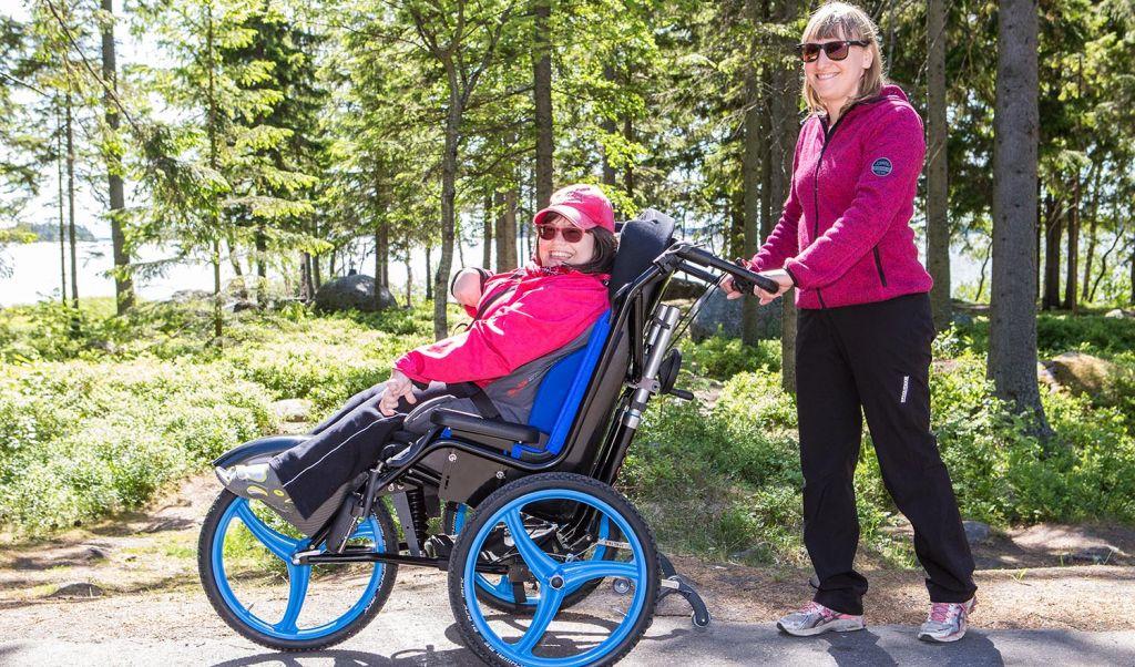 On kesä ja aurinko paistaa. Nuori nainen istuu pyörätuoli Largossa ja hymyilee. Nainen avustaa häntä työntämällä välinettä, myös avustaja hymyilee. Taustalla näkyy metsää ja järvi. Kuva: Ann-Britt Bada.