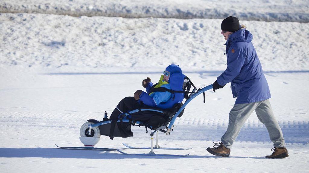 On talvi ja aurinko paistaa. Nuori poika istuu Hippocampe maastopyörätuolissa, johon on kiinnitetty sukset renkaiden tilalle. Mies avustaa työntämällä maastopyörätuolia lumella. Kuva: Janne Ruotsalainen.