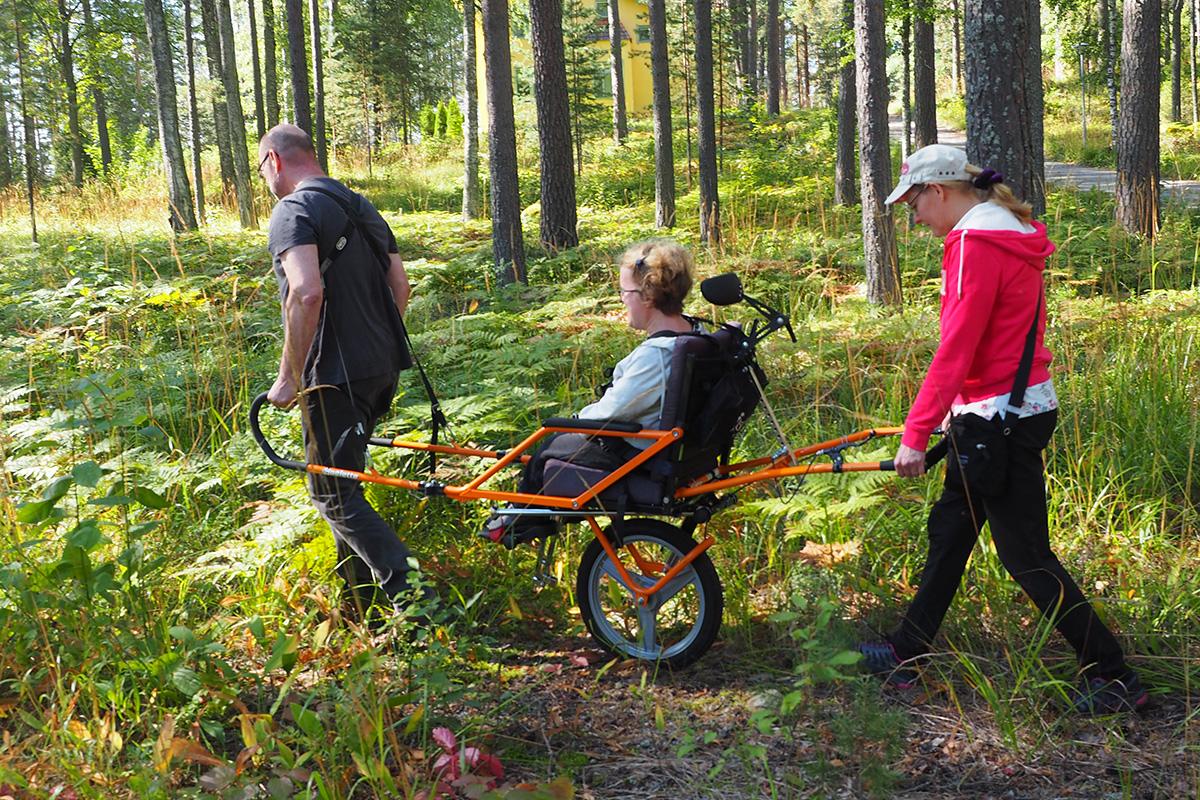 Maastokärryn ja avustajien avulla liikkumassa luonnossa.