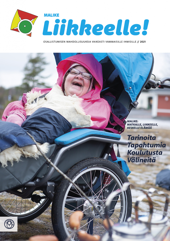 Liikkeelle-lehden kannessa on sinisissä JOSI-Wismi -rattaissa istuva nainen, joka paistaa makkaraa iloinen ilme kasvoillaan.