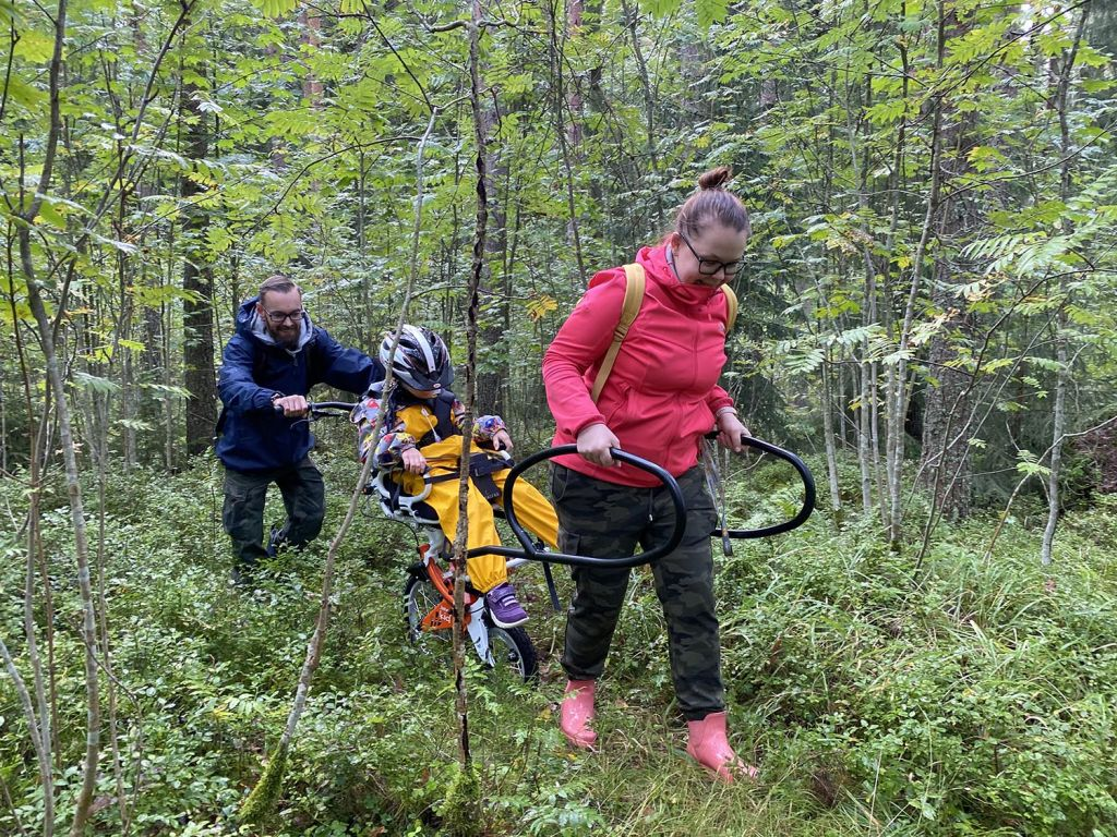 On kesä, poika keltaisissa sadehousuissaan istuu Joelette Kid -maastokärryn kyydissä metsäretkellä. Pojalla on pyöräilykypärä päässään. Kärryä työntää sinitakkinen isä ja vetää äiti, punaisessa takissaan.