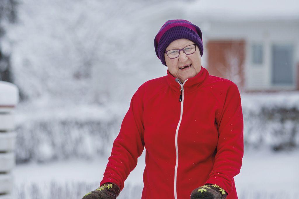 Ikääntynyt nainen lenkillä rollaattorin kanssa lumisessa maisemassa.