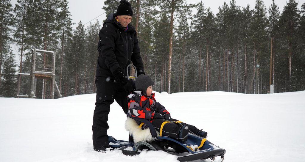 Isä ja poika laskevat mäkeä. Vaikeasti vammainen poika istuu Snow Comfort -kelkassa, jossa on selkänoja ja pääntuki.