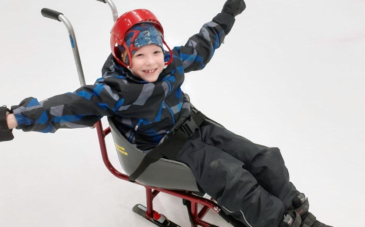 Iloisen näköinen poika istuu punaisessa luistelukelkassa, jossa on selkänoja. Hän nostaa käsiään onnellisen näköisenä ilmaan.