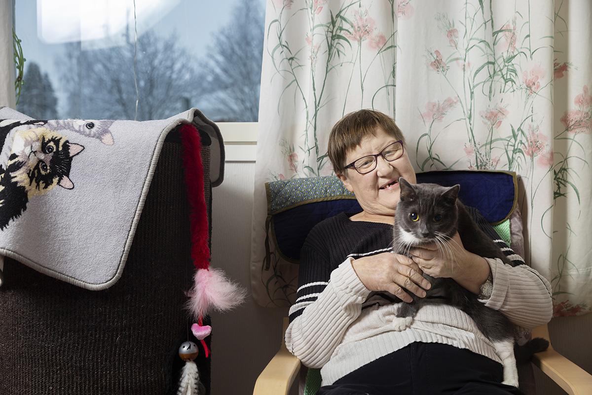 Nainen pitää kissaa sylissään.