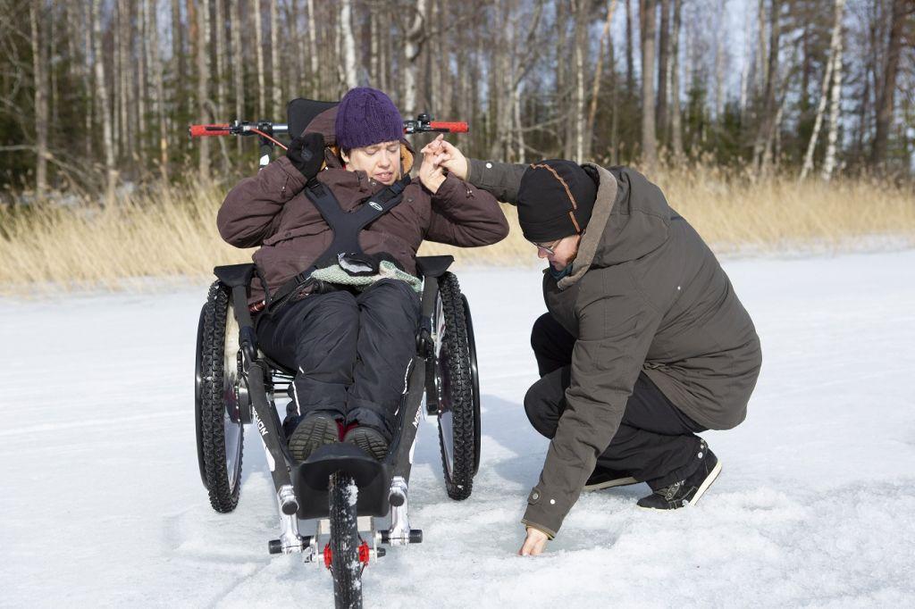 Kaksi ihmistä jäällä kokeilemassa kylmää vettä.