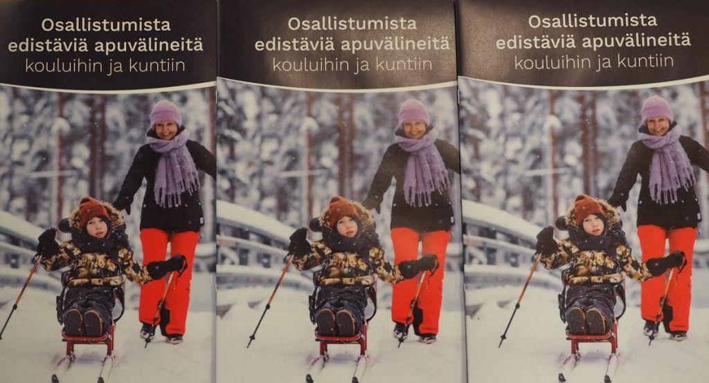 Vierekkäin kolme oppaan Osallistumista edistäviä apuvälineitä kouluihin ja kuntiin kansilehteä. Kannessa oppaan nimi sekä kuva jossa poika hiihtää hiihtokelkalla ja aikuinen kävelee hänen perässään.