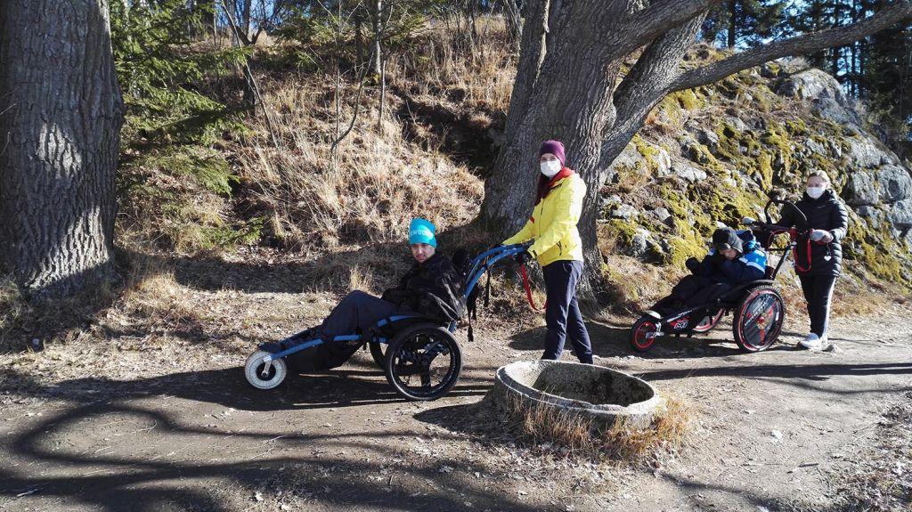 Kuvassa on vaikeasti vammaisia aikuisia avustajineen retkellä toimintavälineiden avulla.