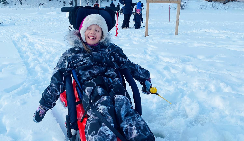 Vaikeasti vammainen tyttö istuu Snow Comfort -kelkassa, jossa on tukeva selkäosa. Hänen kädessään on pilkki.