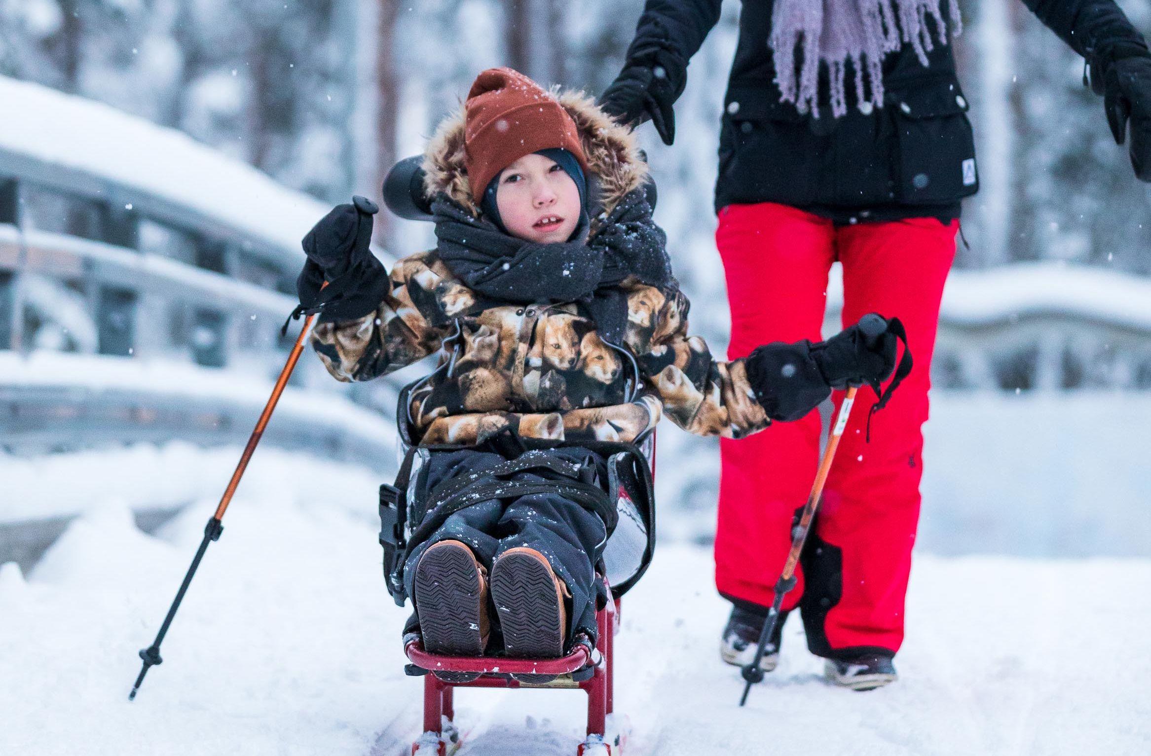 Poika hiihtää hiihto- ja luistelukelkalla istuen. Kelkassa on selkänoja ja niskatuki, jotka mahdollistavat vaikeasti vammaisen lapsen hyvän asennon kelkassa.