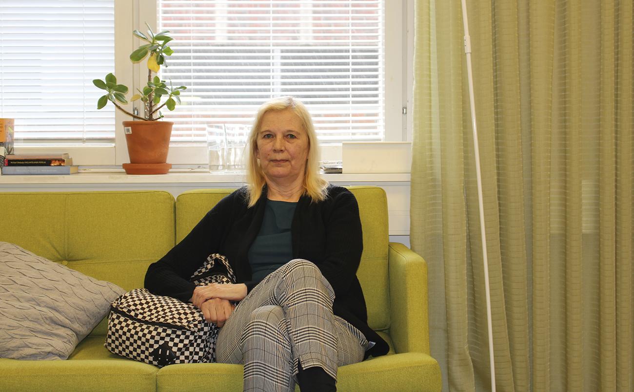 Paula Vesterinen istuu Tulppaanitalolla limen vihreällä sohvalla ja katsoo kameraan.