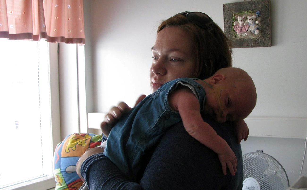Äiti pitää pientä poikaa sylissä