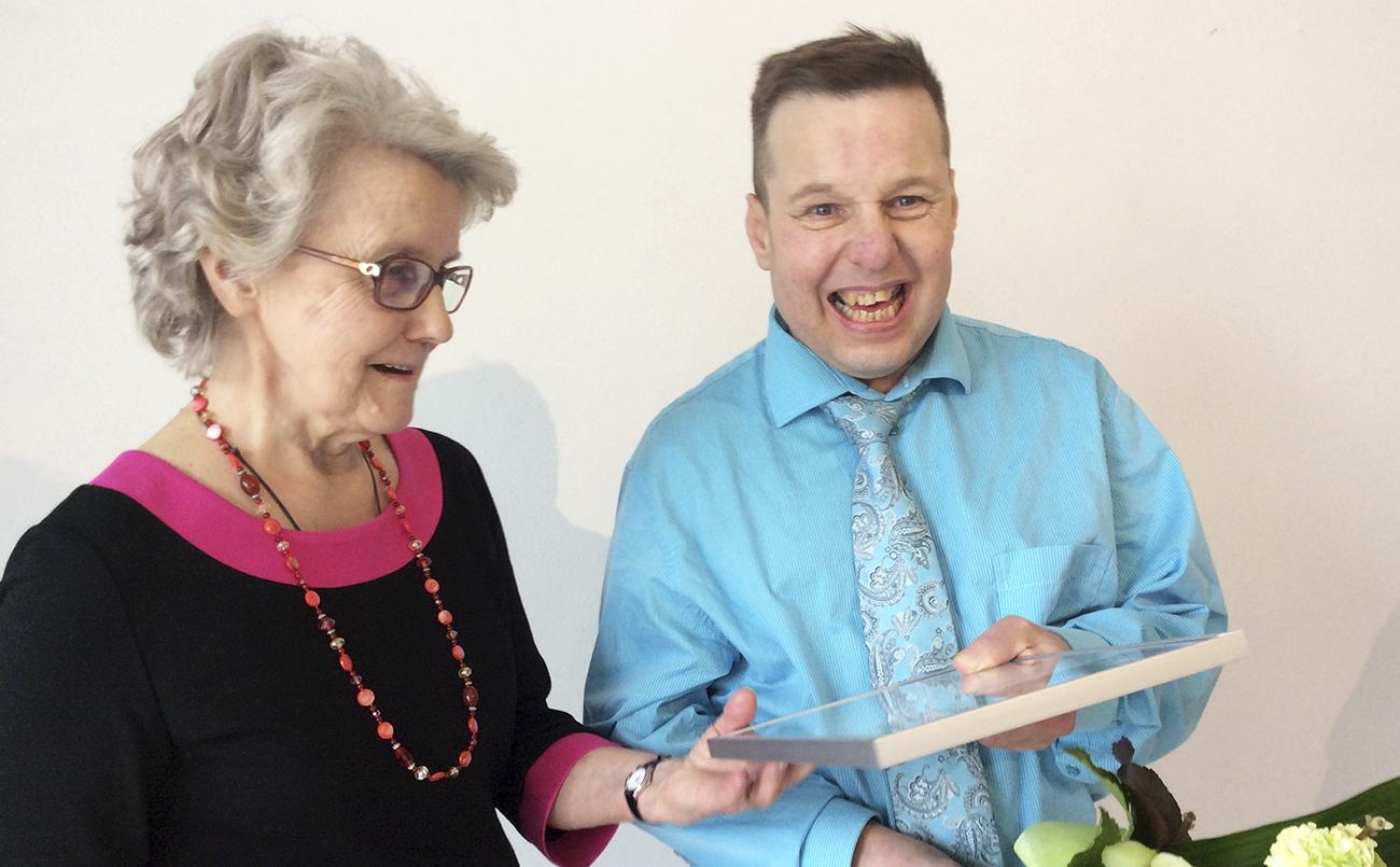 Äiti ja poika iloitsivat yhdessä, kun Pasi Soukkala oli valittu Kettukin vuoden taiteilijaksi vuonna 2016. He katsovat yhdessä kehystettyä kunniakirjaa jota Pasi pitää kädessä.