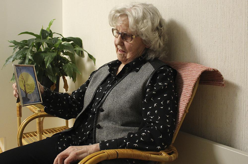 Eila Soukkaa istuu keittiössä ja pitelee kehystettyä postikorttia, jonka Pasi on lähettänyt hänelle.