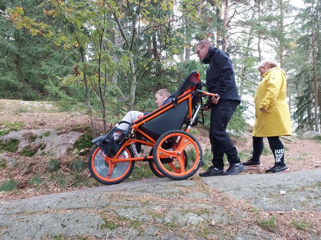 perhe ulkoilee luontopolulla Kangoo-rattaita työntäen