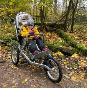 lapsi keltaisessa takissa istuu monitoimirattaissa aurinkolasit päässä, syksyinen metsä taustalla