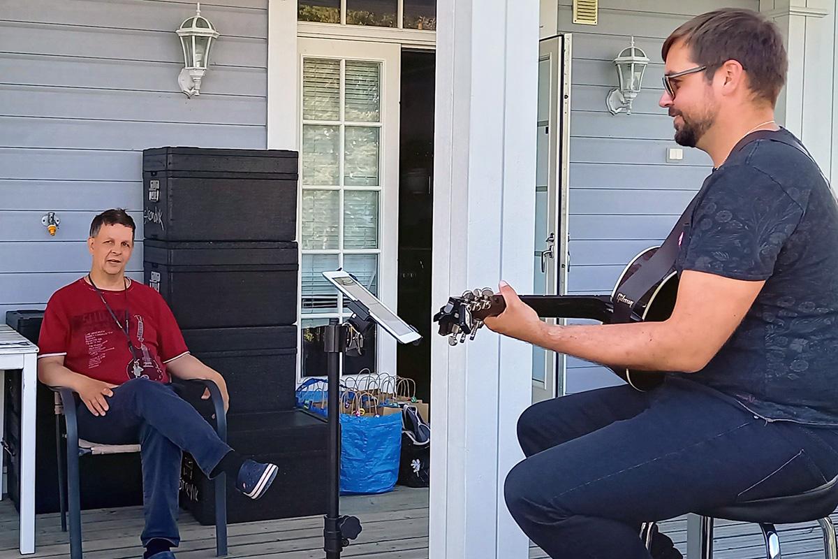 Avaralla terassilla mies soittaa kitaraa kuulijalleen.