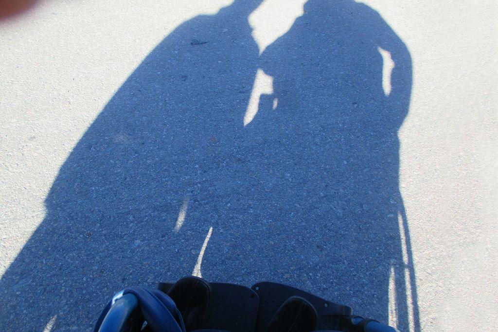Kahden ihmisen varjot näkyvät aurinkoisella tiellä.