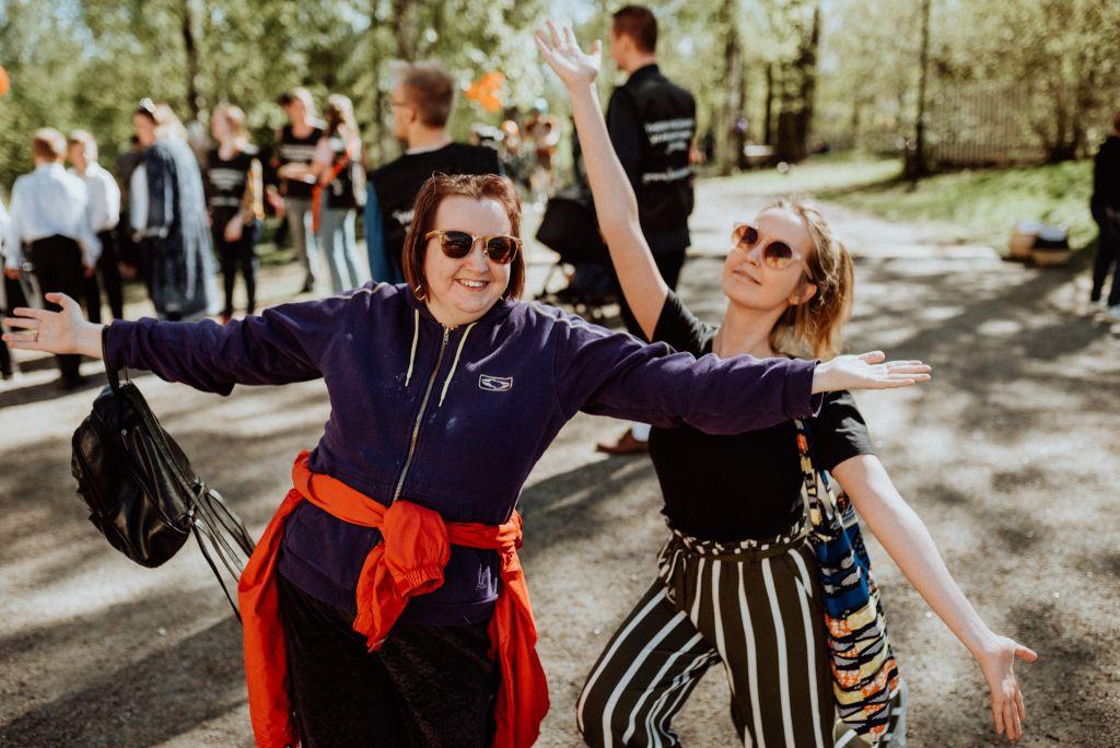 Kaksi naita poseraa kameralle hymyillen ja kädet ilmassa